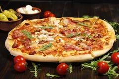 Pizza med bacon, korvar, skinka, tomaten och oliv Stänk med arugula och som tjänar som med tomaten och ost Pizzarestaurang Royaltyfri Foto