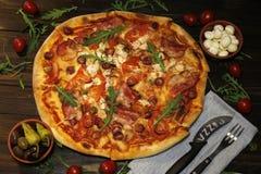 Pizza med bacon, korvar, skinka, tomaten och oliv Stänk med arugula och som tjänar som med tomaten och ost Pizzarestaurang Royaltyfri Fotografi