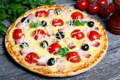 Pizza med bacon, oliv och tomaten Fotografering för Bildbyråer