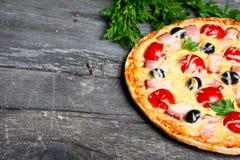 Pizza med bacon, oliv och tomaten Arkivbild