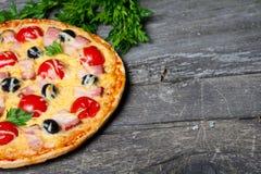 Pizza med bacon, oliv och tomaten Arkivfoto
