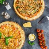 Pizza med bacon, ost och tomaten på mörk bakgrund Lekmanna- lägenhet Top beskådar Läcker matbakgrund arkivfoton