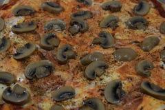 Pizza med champinjoncloseupen som en bakgrund Royaltyfri Foto