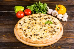 Pizza med champinjoner och ost på en mörk träbakgrund med royaltyfria foton