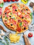 Pizza med champinjoner, salami och tomater royaltyfri fotografi