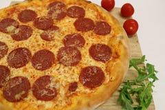 Pizza med den körsbärsröda tomaten och rucola läcker italiensk pizza Peperonipizza med den körsbärsröda tomaten och rucola Arkivbild