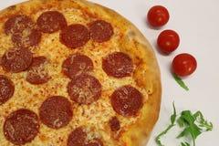 Pizza med den körsbärsröda tomaten och rucola läcker italiensk pizza Peperonipizza med den körsbärsröda tomaten och rucola Royaltyfri Fotografi