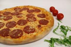 Pizza med den körsbärsröda tomaten och rucola läcker italiensk pizza Peperonipizza med den körsbärsröda tomaten och rucola Royaltyfri Bild