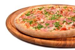 Pizza med den skinkatomaten och löken på ett träuppläggningsfat Fotografering för Bildbyråer