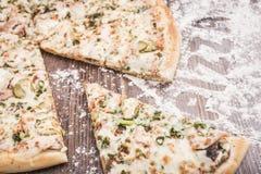 Pizza med ett snittstycke på en träbakgrund som strilas med mjöl Arkivfoton