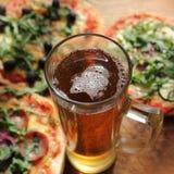 Pizza med exponeringsglas av öl Arkivfoto