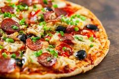 Pizza med fegt kött, Mozzarellaost, peperoni, tomat, oliv, salami arkivbild