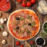 Pizza med ingrediensen arkivbild
