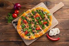 Pizza med kalvk?ttet och torkade tomater p? en tr?bakgrund arkivfoto