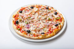Pizza med löken och skinka, ost och tomat Vit bakgrund arkivbild