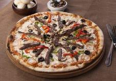 Pizza med nötköttstycken på en brun bakgrund arkivfoto