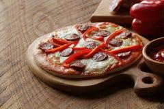 Pizza med peperonin, paprica på trätabellen Top beskådar Arkivbild