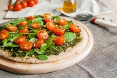 Pizza med pesto, spenat och körsbärsröda tomater Royaltyfri Foto