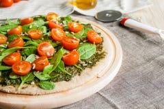 Pizza med pesto, spenat och körsbärsröda tomater Arkivfoton