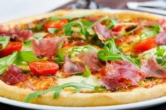 Pizza med prosciuttoen, nya tomater och Rucola Royaltyfri Fotografi