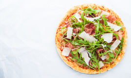 Pizza med prosciuttoen & x28; parma ham& x29; , arugula & x28; salladrocket& x29; och parmesan på bästa sikt för vit bakgrund arkivbild