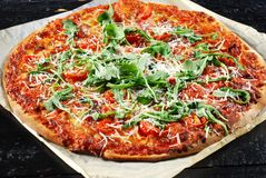 Pizza med proscuitto, tomater och arugula Fotografering för Bildbyråer