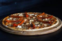 Pizza med salami och örter på kritabräde Royaltyfria Bilder