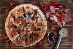 Pizza med salami-, peperoni-, oliv- och champinjonlögner på en lantlig tabell för planka bredvid röd peppar, tomater, ost, korv, royaltyfri bild