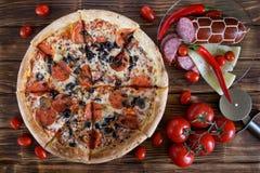 Pizza med salami-, peperoni-, oliv- och champinjonlögner på en lantlig tabell för planka bredvid röd peppar, tomater, ost, korv o royaltyfria bilder