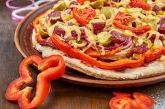 Pizza med salami, tomater, spansk peppar, lökcirklar, gröna oliv, havre, ost och kryddor på en mörk platta royaltyfri fotografi