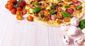 Pizza med salamigrönsaker och kryddor på en vit träbakgrund med kopieringsutrymme Arkivbild
