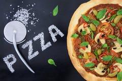 Pizza med skäraren och saltar på rolig design Arkivfoto