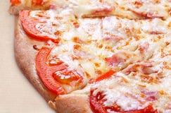 Pizza med skinka, tomaten och ost royaltyfri bild