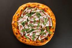 Pizza med skivad bästa sikt för bacon- och arugulasallad Royaltyfri Foto