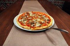 Pizza med tomaten och champinjoner på tabellen royaltyfria foton