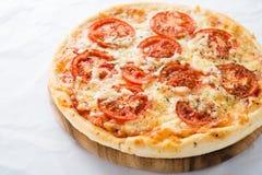 Pizza med tomaten, ost och torr basilika på det vita bakgrundsslutet upp Royaltyfri Fotografi