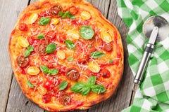 Pizza med tomater, mozzarellaen och basilika Royaltyfri Bild