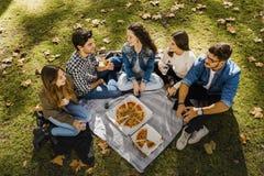 Pizza med vänner arkivbilder