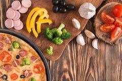 Pizza met broccoli, erwten, worst, olijven, peper en tomaten stock foto's