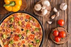 Pizza met broccoli, erwten, worst, olijven, peper en tomaten stock foto