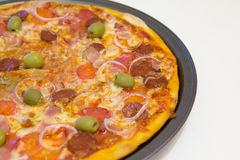 Pizza met chorizo, salami, bacon, uien en olijven Stock Foto