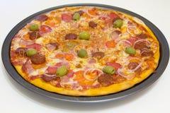 Pizza met chorizo, salami, bacon, uien en olijven Royalty-vrije Stock Afbeeldingen