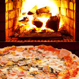 Pizza met ham, paddestoel en open brand in oven royalty-vrije stock fotografie