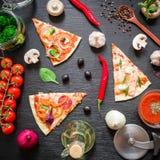 Pizza met ingrediënten en groenten op donkere lijst Vlak leg, hoogste mening Gesneden pizzapatroon royalty-vrije stock afbeeldingen