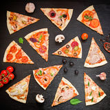 Pizza met ingrediënten en groenten op zwarte achtergrond Vlak leg, hoogste mening Gesneden pizzapatroon stock fotografie