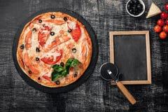 Pizza met kaas, forel, tomaten, olijven en garnalen op schoolbord stock foto's