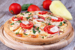 Pizza met kip, tomaten en kaas op een houten raad Stock Fotografie