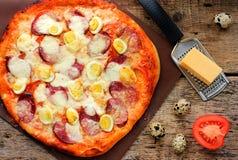 Pizza met kwartelseieren, worst, kaas en tomaten op houten Stock Afbeelding