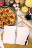 Pizza met notitieboekje en ingrediënten Royalty-vrije Stock Foto