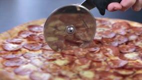 Pizza met salami in de helft met een speciaal mes voor pizza wordt gesneden die stock footage